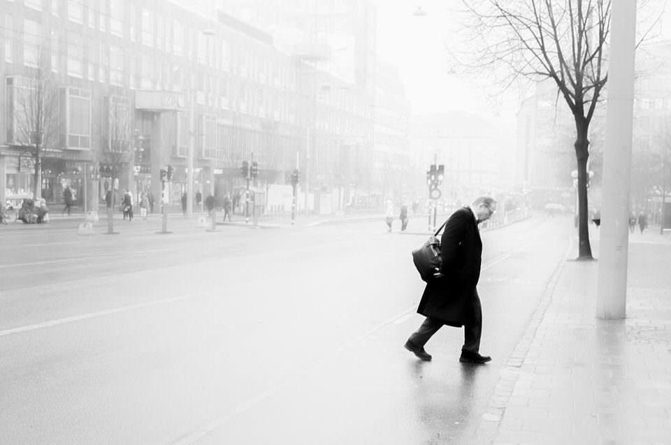 Mann geht über eine verregnete Straße