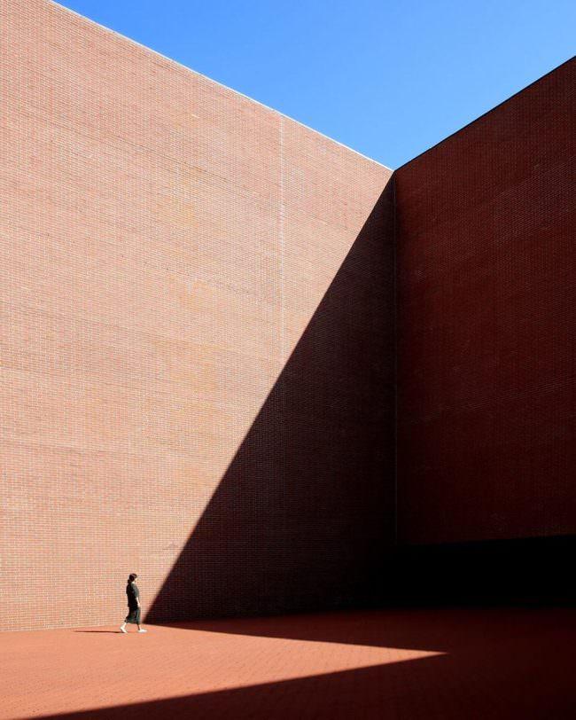 Person an einer großen Mauer am Ende eines Schattens