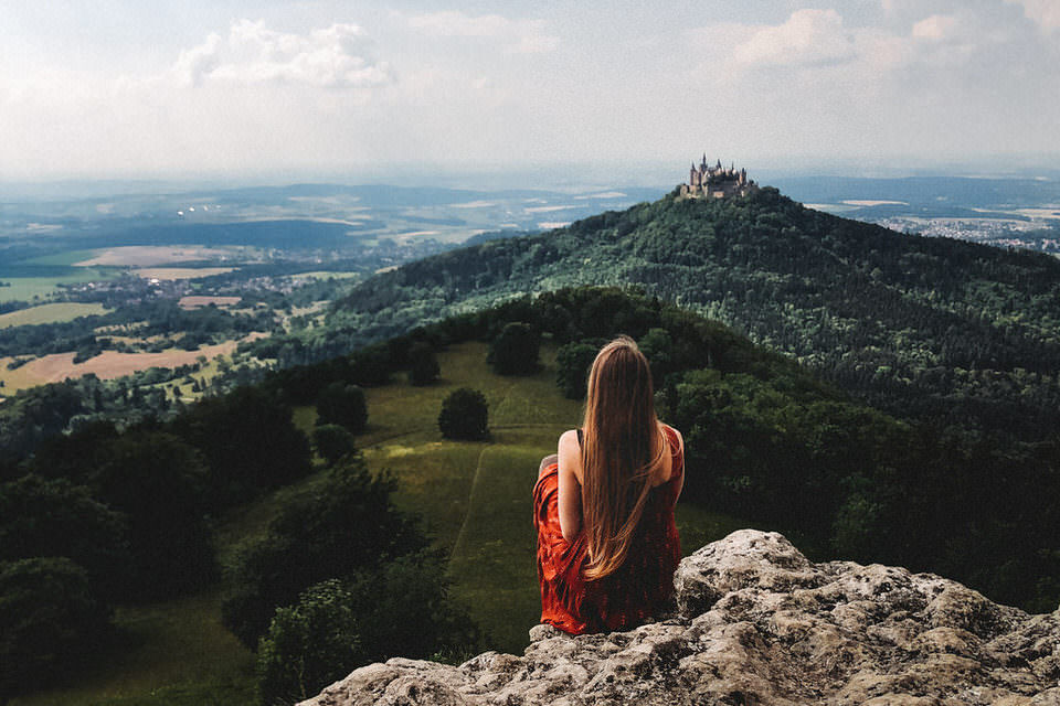 Frau sitzt auf Felsen mit Blick auf einer Burg