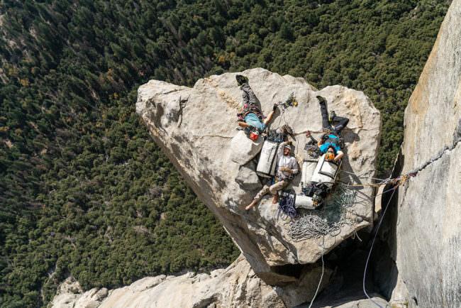 Bergsteiger*innen ruhen sich auf einem Vorspung aus