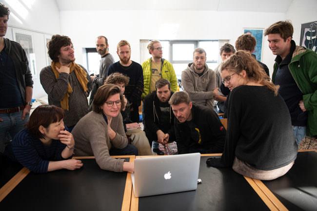 Menschen um einen Laptop