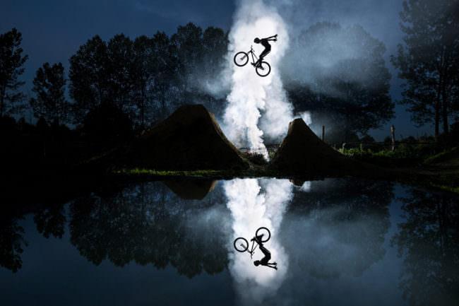 Radfahrer über rauchendem Boden mit Spiegellung