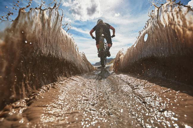 Radfahrer fährt durch eine Pfütze