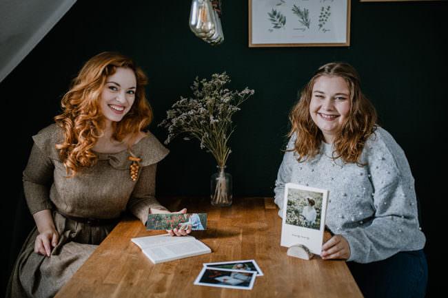 Zwei Frauen an einem Tisch zeigen Fotokalender