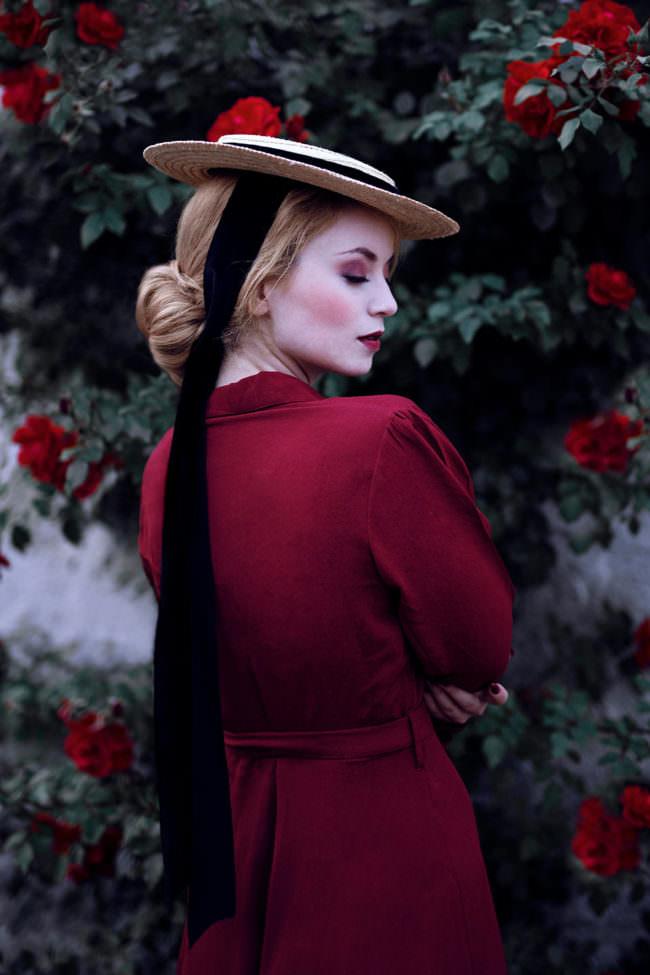 Frau mit Hut und rotem Kleid vor einer Rosenhecke
