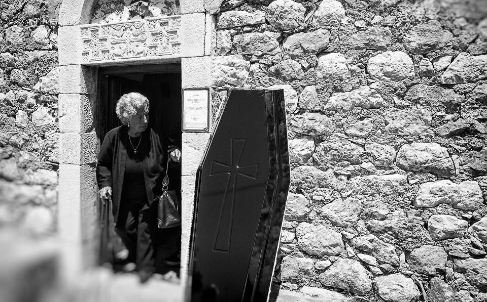 Frau geht aus einem Haus. An der Wand lehnt ein Sarg