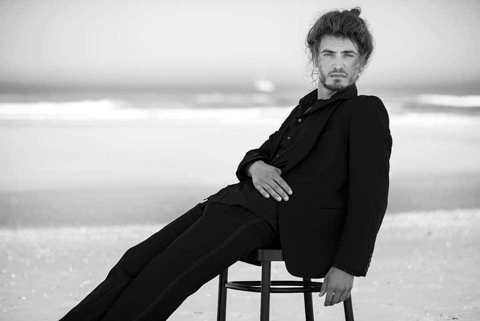 Mann auf einem Stuhl am Strand