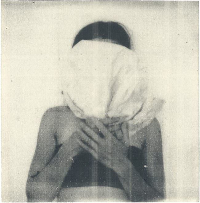 Frau hält ein Kissen auf dem Kopf
