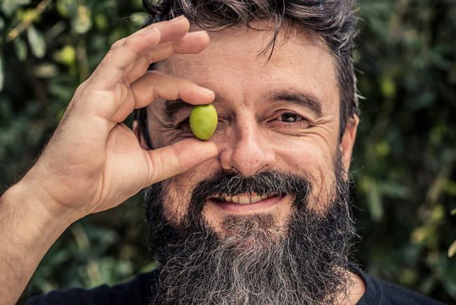 Mann hält sich eine Olive vor das Auge