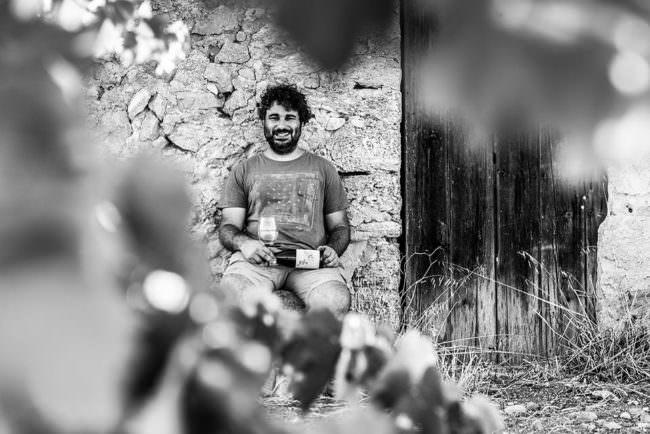 Mann mit Weinflasche sitzt vor einem Haus