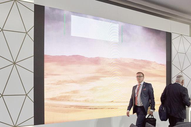 Person läuft vor einer Wand mit Wüstenlandschaft vorbei.