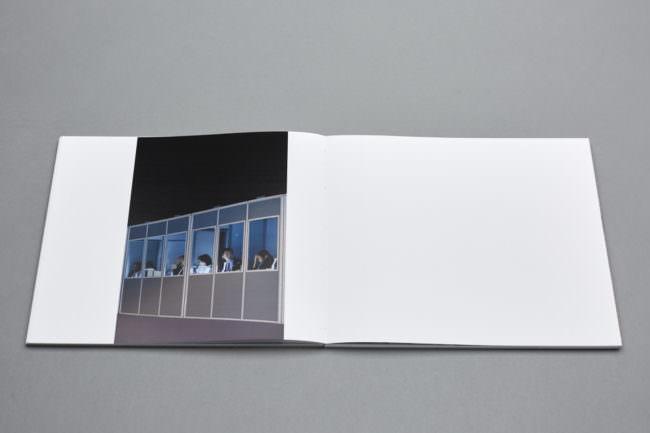 Aufgeklapptes Buch mit Bild von Personen an Glasfront