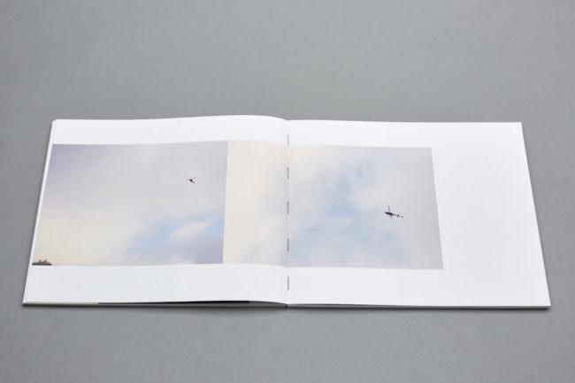 Auf geklapptes Buch mit zwei Fotografien von Himmel