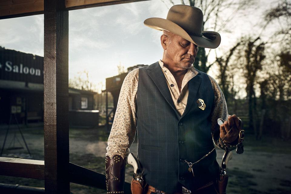 Mann in Wild-West-Outfit schaut auf eine Uhr