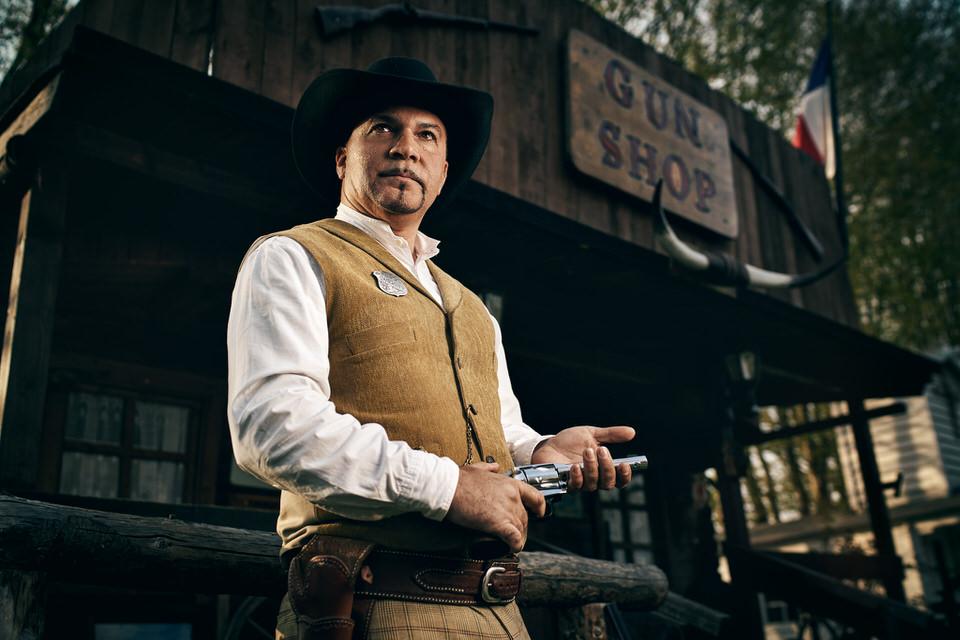 Mann in Wild-West-Outfit mit Gewehr