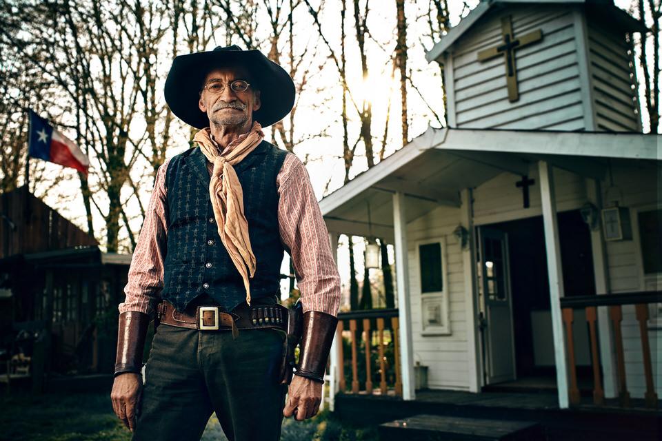 Mann in Wild-West-Outfit vor einer Kirche