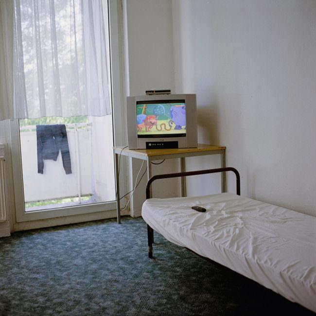 kleiner Fernseher vor einem Bett