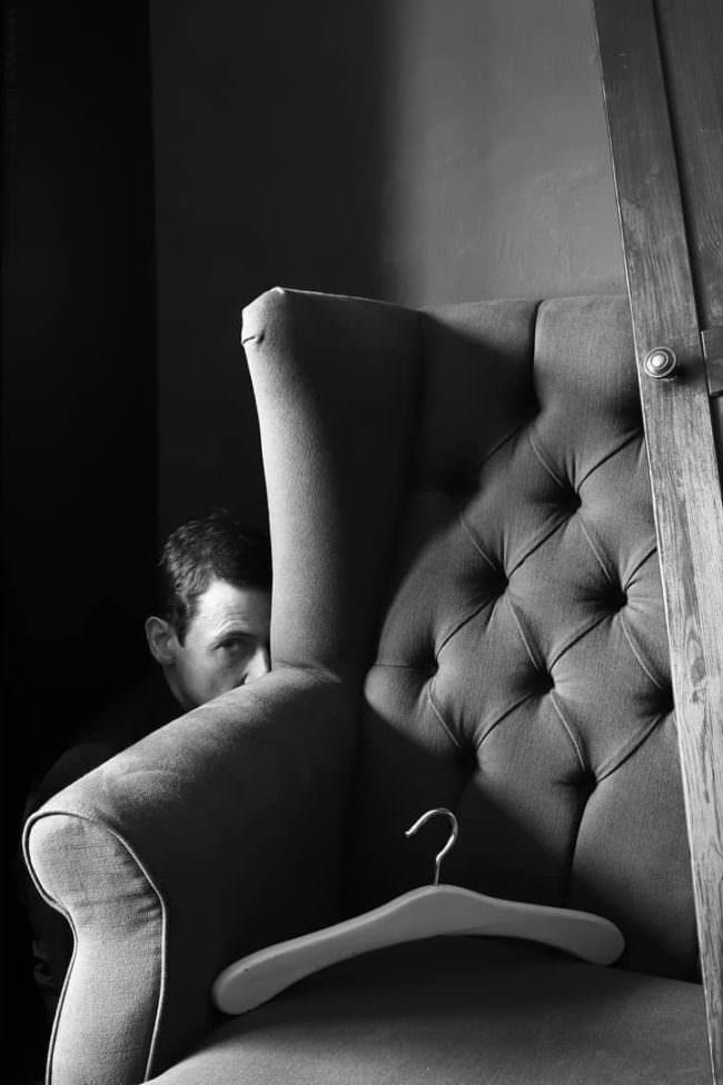 Mann versteckt hinter Sessel