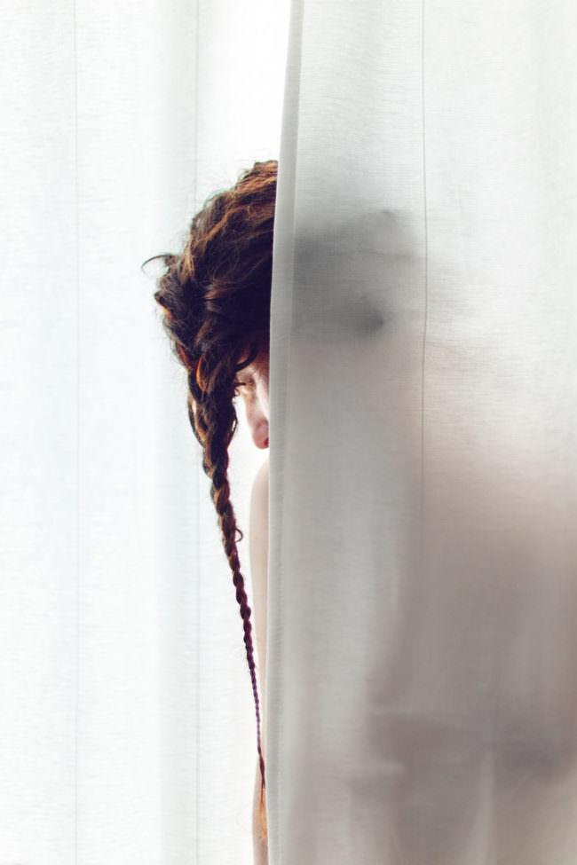 Person mit Zopf hinter einem transparentem Vorhang