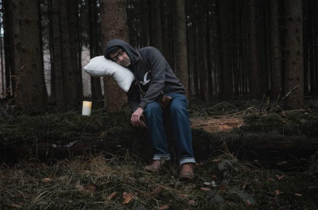 Mann leht mit einem Kissen an einem Baum