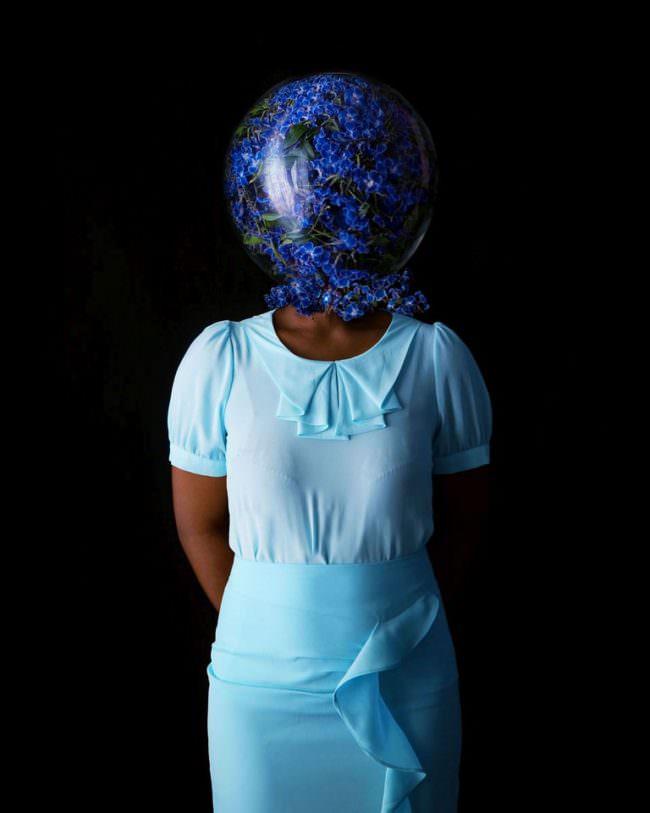 Frau mit Glas über dem Kopf, gefüllt mit blauen Blüten