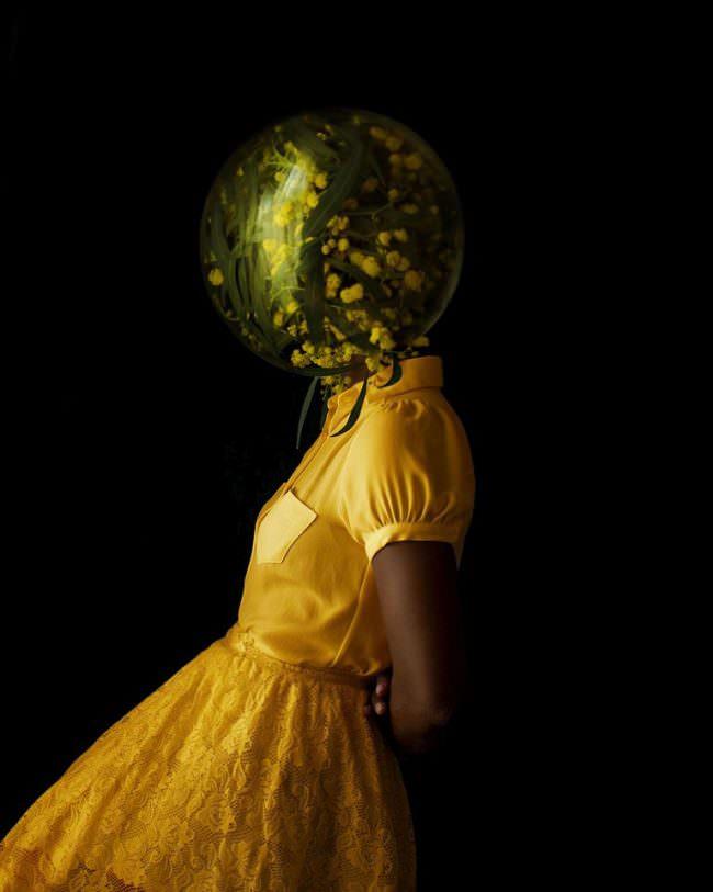 Frau mit Glas über dem Kopf, gefüllt mit gelben Blüten