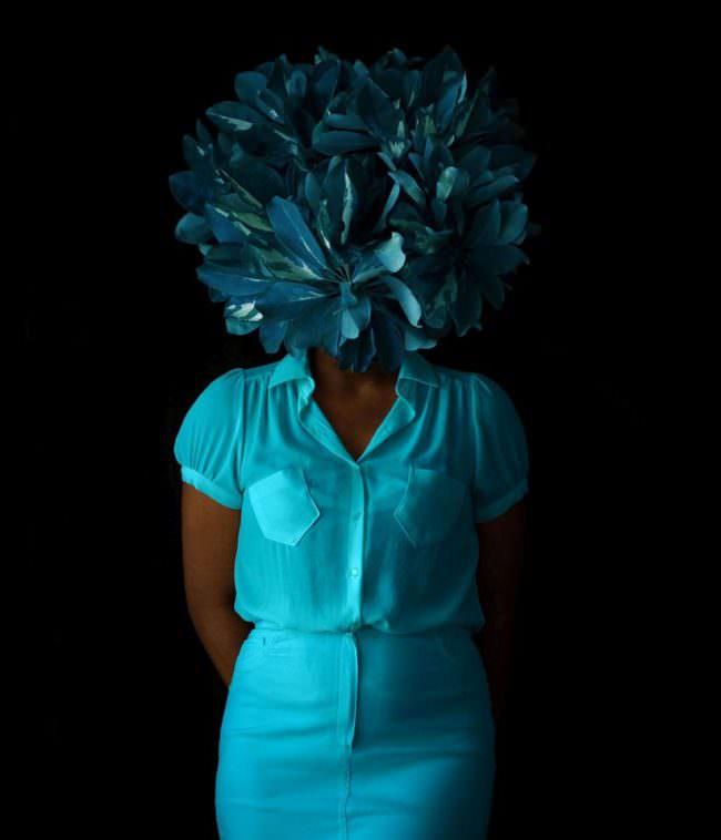Frau mit blauen Blättern vorm Gesicht