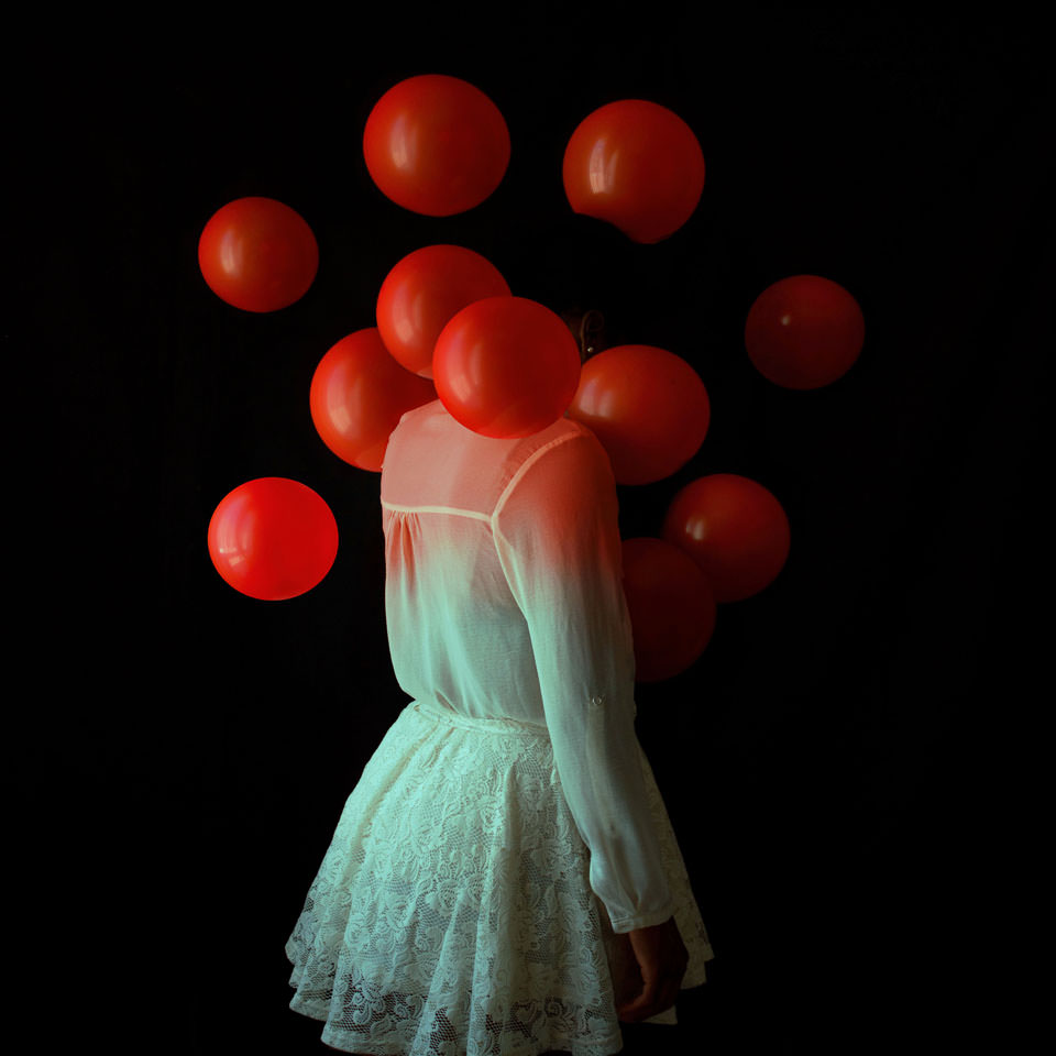 Frau in Kleid mit roten Ballons