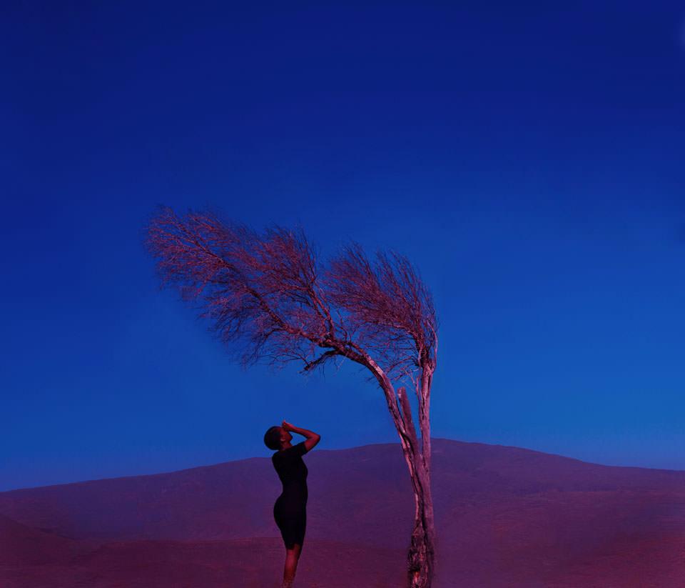 Frau steht in surrealer blau-violetter Landschaft