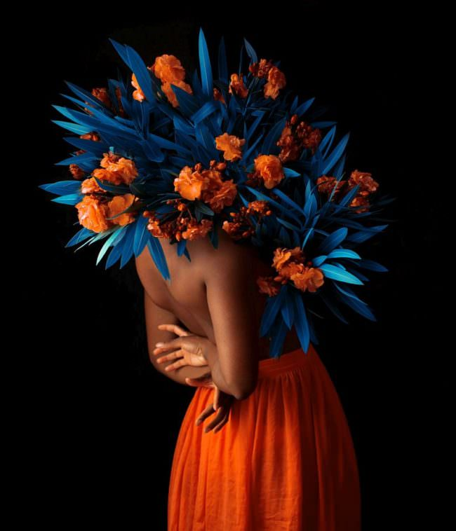 Frau mit Kopf in Blüten und Blättern