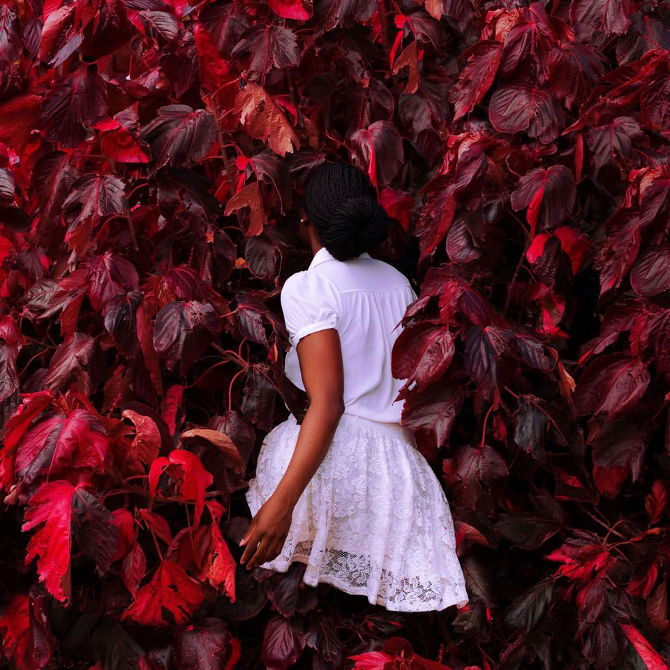 Frau in roter Blätterwand