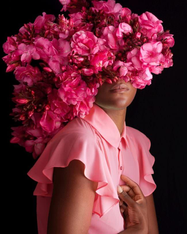 Frau mit Maske aus pinken Blüten