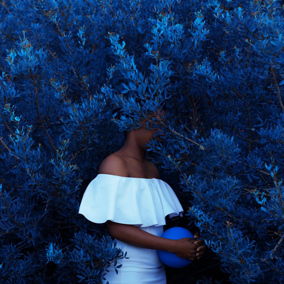Frau steht in blauem Gebüsch