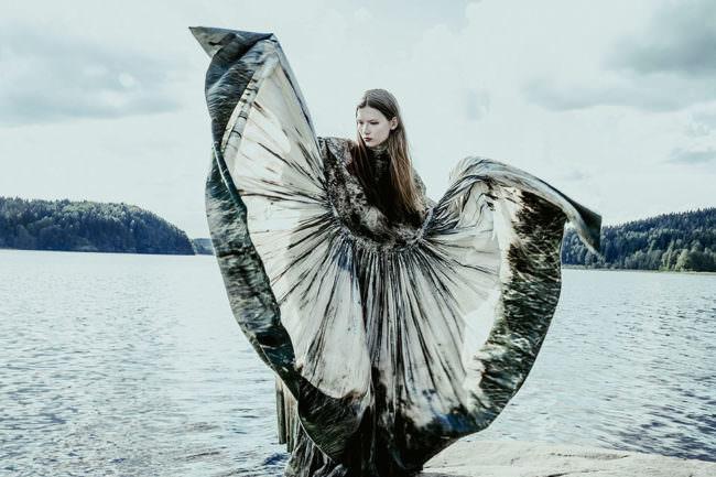 Frau wirft ihr Kleid in die Luft vor einem See