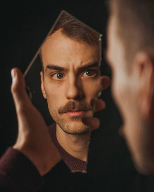 Mann sieht sich in einer Spiegelscherbe