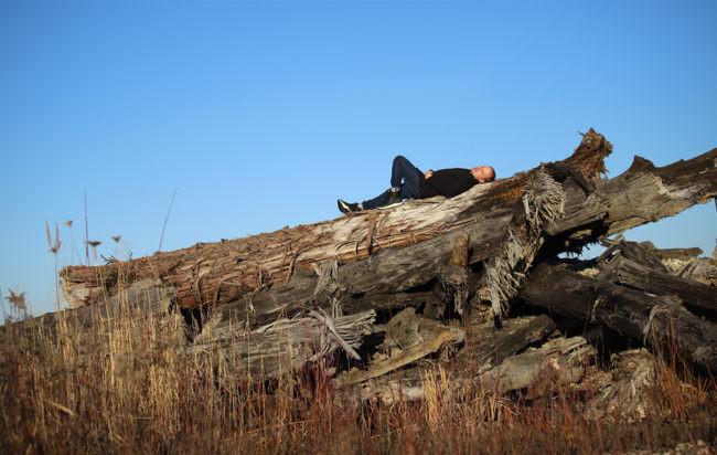 Mann liegt auf einem Baumstamm