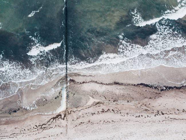 Drohnenaufnahme von Wellen am Strand