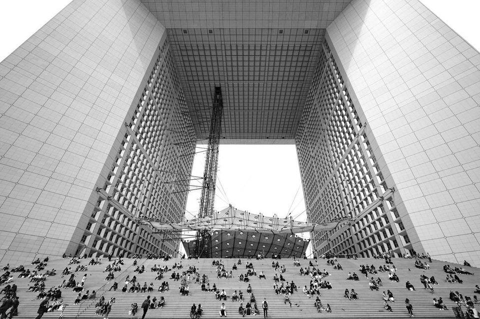 Menschen sitzen auf einer Treppe vor einer großen Architektur