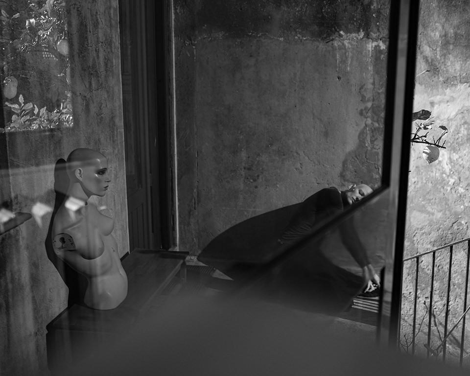 Eine Person liegt auf einer Treppe. Im Vordergrund eine Schaufensterpuppe