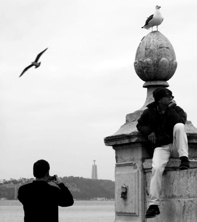 Eine Person sitzt auf einer Mauer, die andere fotografiert