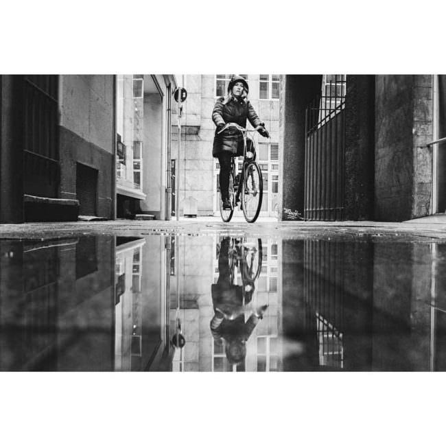 Radfahrerin spiegelt sich in einer Pfütze