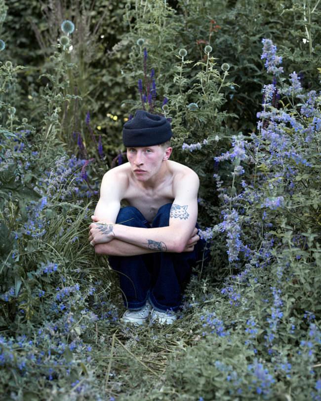 Mann mit Mütze zwischen Blumen