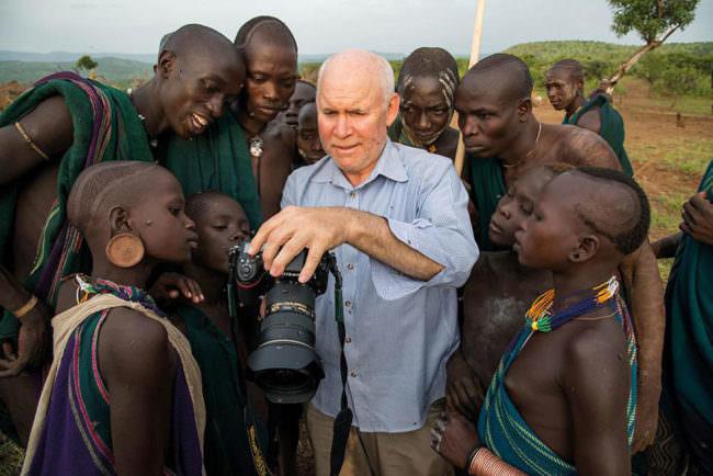 Mann mit Kamera zeigt einer Gruppe Menschen die Fotos