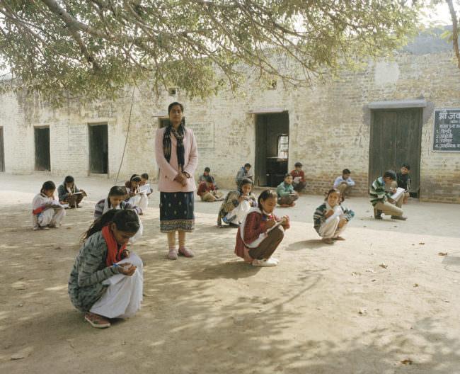 Kinder hocken mit Stiften und Notizzetteln vor einem Haus unter einem Baum