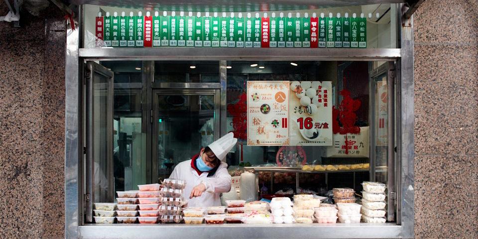 Eine Frau mit Mundschutz sitzt im Fenster eines Ladens.