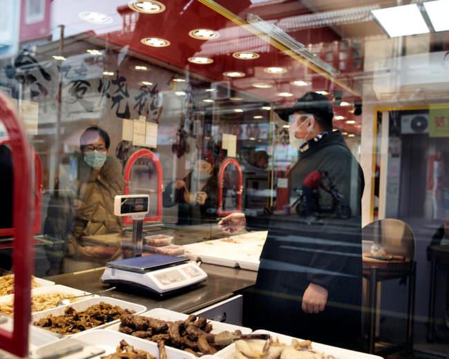 Zwei Menschen mit Mundschutz stehen in einem Geschäft