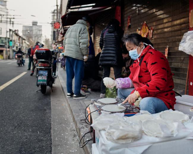 Eine Frau mit Mundschutz kocht am Straßenrand