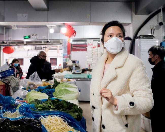 Frau mit Mundschutz vor einem Gemüseregal