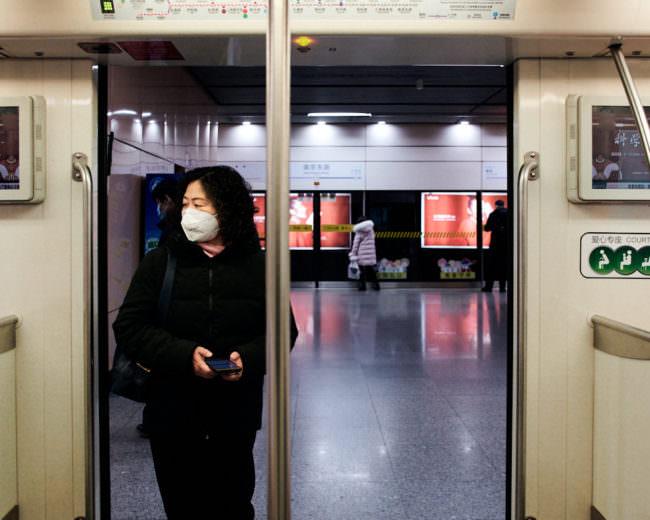 Eine Frau mit Mundschutz steigt in einen Zugwaggon