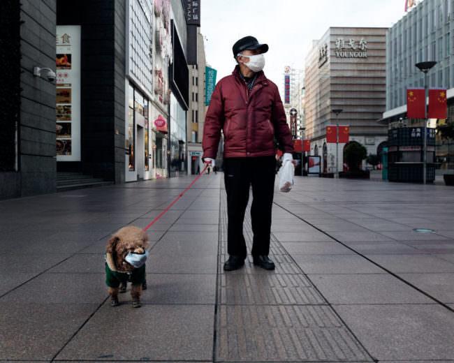 Eine Person mit Mundschutz geht mit einem Hund mit Mundschutz spazieren